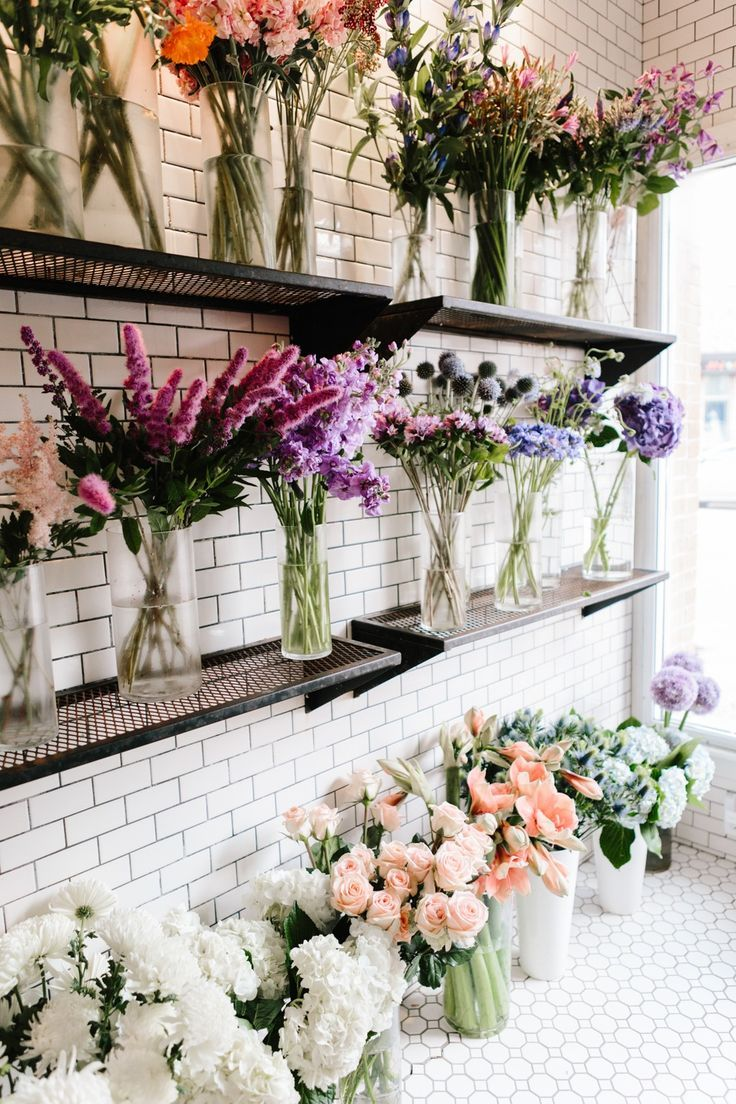 Multicolor flower assortment on shelves; purples, pinks, Peach, green. Beautiful.