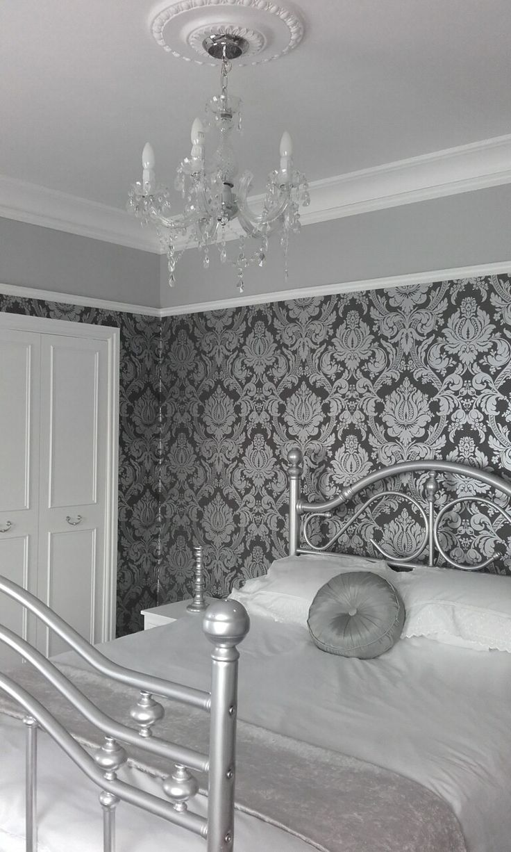 Shabby chic bedroom. Picture rail and cornice. Ceiling rose and chandelier. Headboard and footboard up cycled. Silver damask wallpaper.