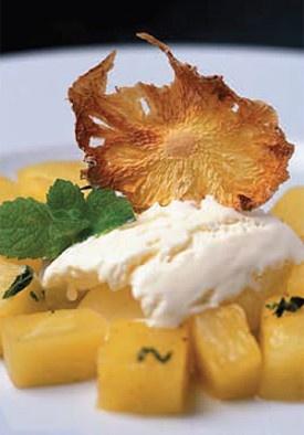 Met rum geflambeerde ananas uit de wok met vanille-ijs en munt