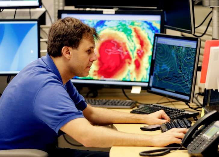 Hurricane specialist Eric Blake monitors the path of Hurricane Matthew at the National Hurricane Center, Tuesday, Oct. 4, 2016, in Miami. Hurricane Matthew roared across the southwestern tip of Haiti with 145 mph winds Tuesday, uprooting trees and tearing roofs from homes in a largely rural corner of the impoverished country as the storm headed north toward Cuba and the east coast of Florida. (AP Photo/Lynne Sladky)