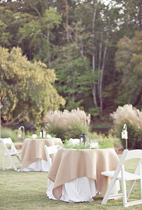 Brides.com: . Burlap and billowing white linens play together for a stark contrast in these cocktail tables, perfectly complementing the springy garden setting.