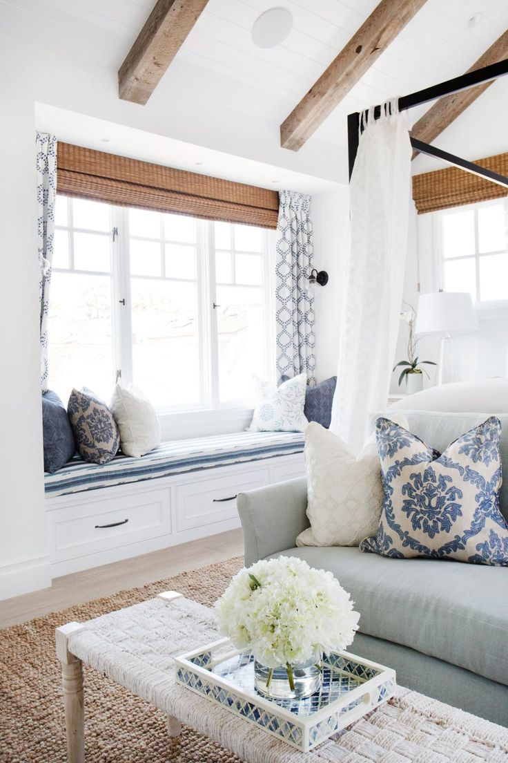 A cushioned window seat provides the perfect spot to enjoy the view in this sea-inspired master bedroom. Adorned with throw pillows and flanked with curtains, the cozy seating area displays a fun assortment of patterns.