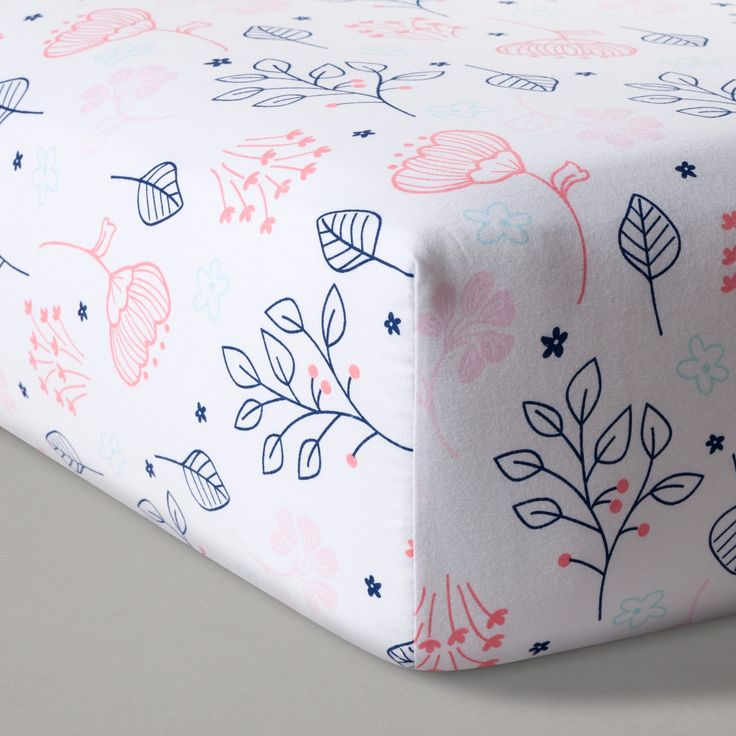 Let baby drift off to sweet dreams of a wooded wonderland with the Navy & Pink Fitted Crib Sheet from Cloud Island™. Navy and pink flowers and leaves gently blow across a white background, bringing a whimsical air to baby's nursery decor. Mix and match with pieces from the Forest Frolic or Floral Fields collections from Cloud Island™ for a woodland theme throughout your nursery.<br><br>Sleep Safely, Little One<br>When putting baby to sleep, &ldq...