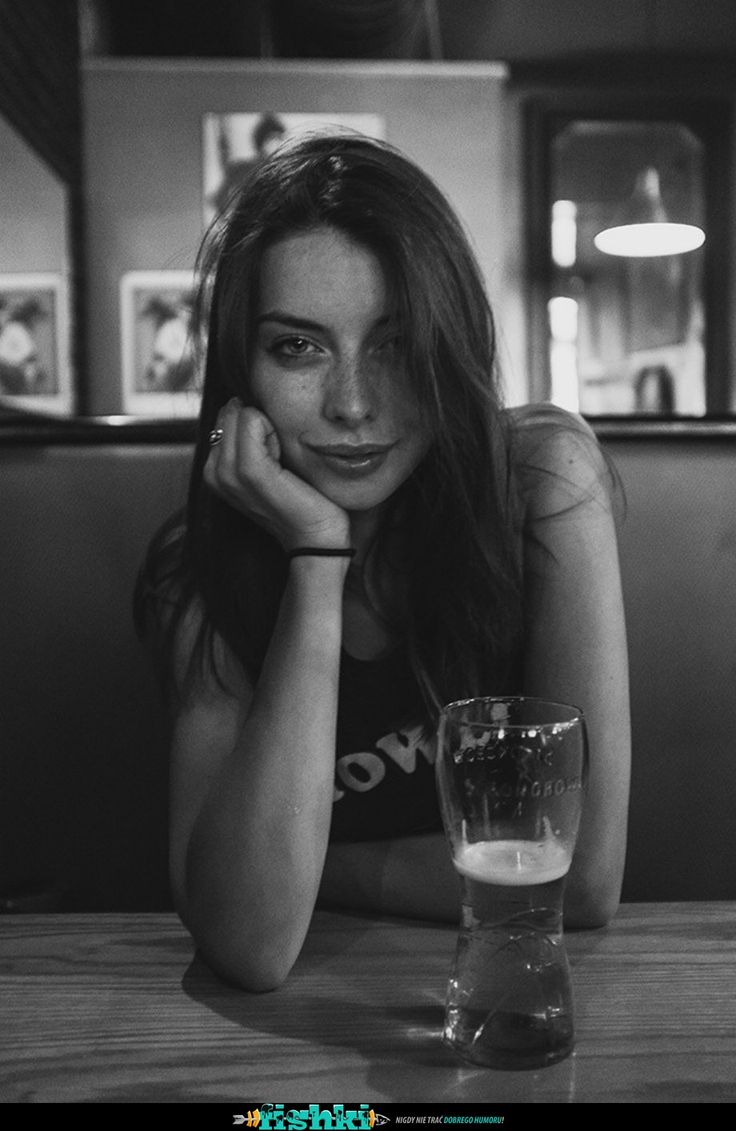 Roxanna Dunlop – Black and white photo portrait of a young woman drinking beer on a table. Long hair, casual short sleeve t-shirt, wrist band, beer glass