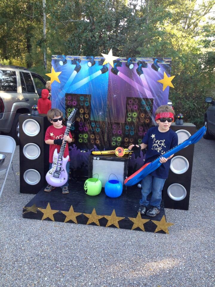 Rock Star Trunk or Treat setup Stage: Pallet & Chipboard, Stars(dollar tree) Backdrop: Scenesetter(Amazon) Speakers: cardboard boxes, spray paint Instruments/microphones(Party City) Costumes:tees mad using vinyl cut on Cricut, glasses/bandana(Dollar Tree) All the kids had a blast taking turns being Rock Stars. It was very interactive!