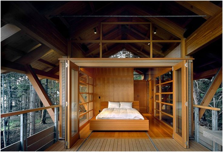 The upper floor bedroom opens up to a deck surrounded by trees with a view of the ocean, and the bed itself can actually be moved out into the open air.