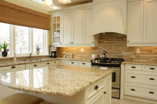 Creamy white cabinets are a great way to brighten up a kitchen while also adding warmth and style. Here, instead of using snow white cabinetry, off-white was used which is more in harmony with the golden tan countertops and backsplash