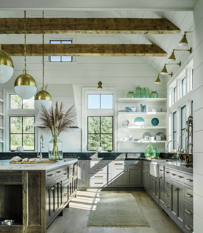 This farmhouse kitchen features vaulted ceiling, exposed beams, shiplap walls, shiplap ceiling, black metal windows, grey lower cabinets, open shelves, large oak island, brass cabinet hardware and brass lighting.
