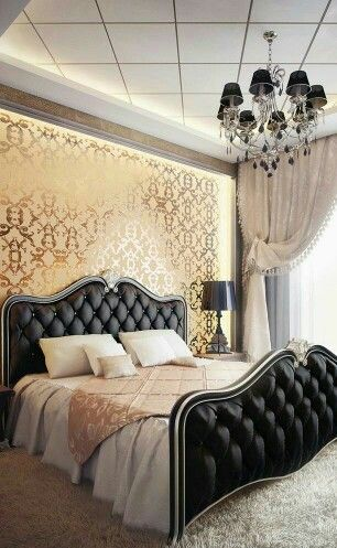 Black bed n golden wallpaper with classic patterns and chandleir giving a royal classy look