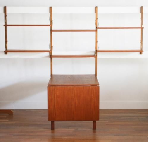 Schitterend wandsysteem met uitklapbare tafel/bureau in teak. Het systeem is in perfecte staat en bestaat uit een uitklapbare tafel/bureau met afmetingen van 80 cm. Breed en 103 cm. Diep (uitgeklapt