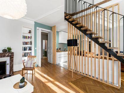 Après : la cuisine prend place derrière l'escalier en métal et le claustra en bois