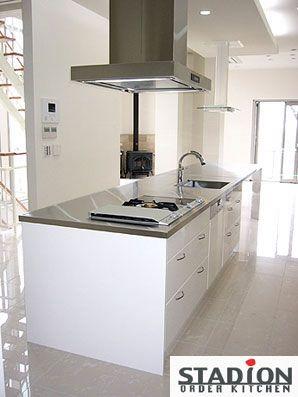 暖炉が似合う白いインテリアの中の白いキッチンは ステンレスで製作した4m70cmのワークトップの存在感が.. http://www.stadion.co.jp/