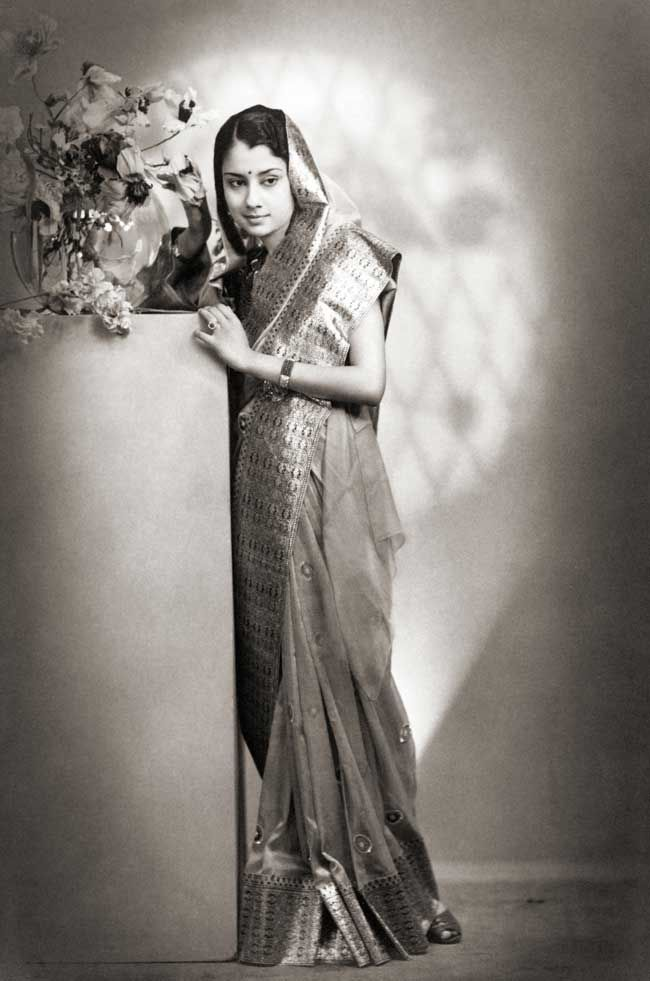 Portrait of Vijayaraje Scindia, c. 1940. A full-length portrait of Vijayaraje Scindia, Maharani of Gwalior (1919-2001), taken c. 1940 by Hamilton Studios, Mumbai. She is dressed here as a princess in a rich gold-bordered sari with her head covered, and leans against a pillar with a flower bouquet. She was born Lekha Divyeshwari, and was politically very active in both houses of parliament.