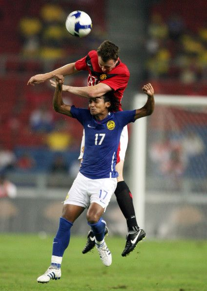 Jonny Evans of  Manchester United (top) competes for a header with Mohd Amri Yahyah of Malaysia XI during the pre-season friendly match between Manchester United and Malaysia XI at Bukit Jalil National Stadium on July 20, 2009 in Kuala Lumpur, Malaysia.