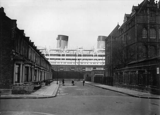 The 26,263 ton Shaw Savill liner Dominion Monarch dwarfs the surrounding houses in Saville Road from her dry dock at the King George V docks in London's Silvertown. (Photo by Harry Todd/Getty Images)