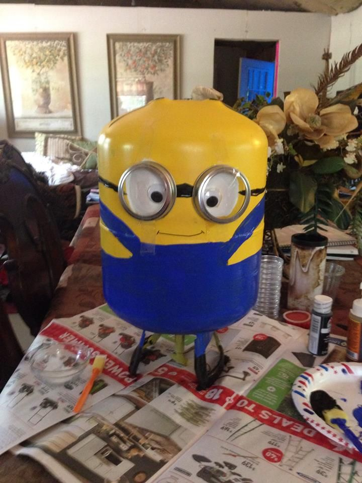 """His is my first minion, Kevin.  He is a re-purposed freon tank.  I spray painted him with Krylon paint,  His coveralls are craft paint.  His eyes are craft paint with googlie eyes glued so he is almost cross eyed.  His """"glasses"""" are canning rings glued on.  The rest of him is craft paint.  I am looking for small black high tops shoes I can fill with quikcrete and his arms will be foam insulation tubes painted yellow and hands child sized black garden gloves.  I"""
