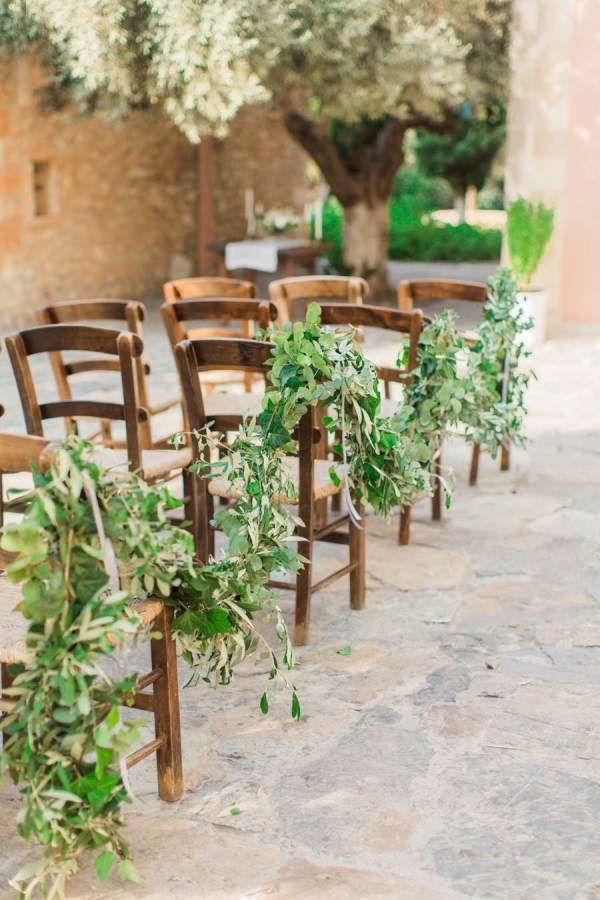 Rustic garland draped ceremony chairs: http://www.stylemepretty.com/little-black-book-blog/2016/02/01/rustic-elegant-crete-destination-wedding-2/   Photography: Anna Roussos - http://www.annaroussos.com/
