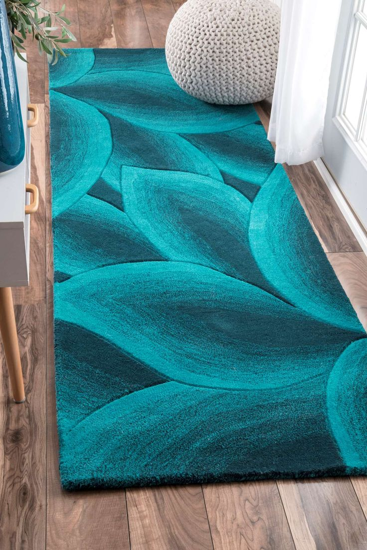 Add a dash of brightness into your interiors with this vibrant, coastal themed hand- tufted woolen rug. The rug is beautiful, thick and plush adding dimension to your interiors with the amazing blend of teals to it.
