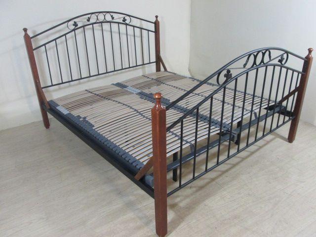 Een 2 persoonsbed van zwart metaal met houten delen in kersenkleur. Het bed is 210 cm x 180 cm. De lattenbodems zijn 200 x 180 cm.
