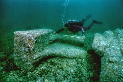Arqueólogo mide los pies de una colosal estatua de granito rojo.