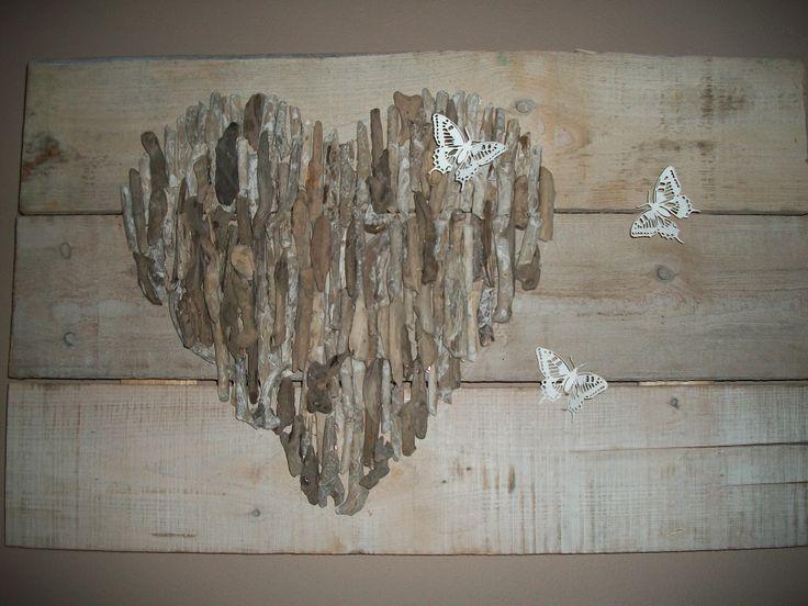 hart van drijfhoutjes op steigerhoutenplanken met vlinders erbij, en klaar is het kunstwerk