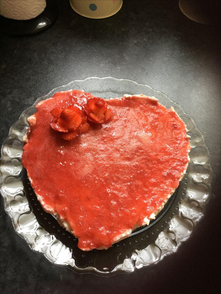 Cheesecake con copertura di salsa di fragole e roselline di fragole