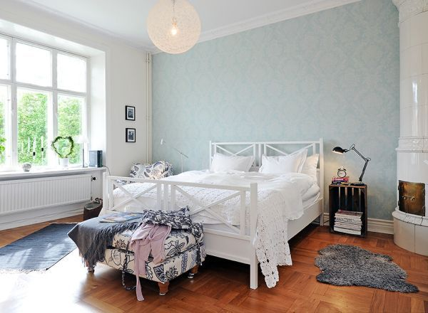 Airy Scadinavian bedroom with wooden flooring and pastel blue wallpaper
