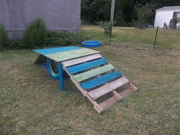 "Goat Platform - Stained plywood top + supports - Red, blue, green, + stained panels on ""stairs"" - No tires underneath"