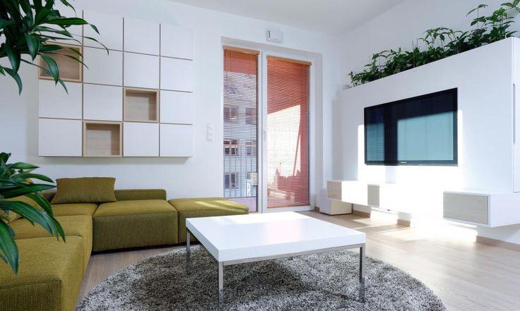 Zariadenie obývačky dvojizbového bytu sme navrhli tak, aby opticky nezmenšovalo malú pôdorysnú plochu miestnosti. Televízna skrinka obsahuje hifi komponenty a televízor, v hornej časti sú hydroponické rastliny. Rohovú sedačku sme navrhli a vyrobili na mieru, aby maximáne využila priestor, rovnako ako knižnicu na stene za sedačkou.