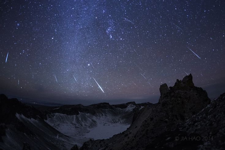 """Geminids 2014. Taken from the summit of Mt. Changbai as a composite of digital frames capturing bright meteors near the shower's peak. Orion is near picture center above the volcanic cater lake. The shower's radiant in the constellation Gemini is to the upper left. The photographer encountered severe wind gusts and minus 34 degree C temperatures near the summit. (Image Credit & Copyright: Jia Hao) Mona Evans, """"Meteor Shower - the Perseids"""" http://www.bellaonline.com/articles/art27461"""