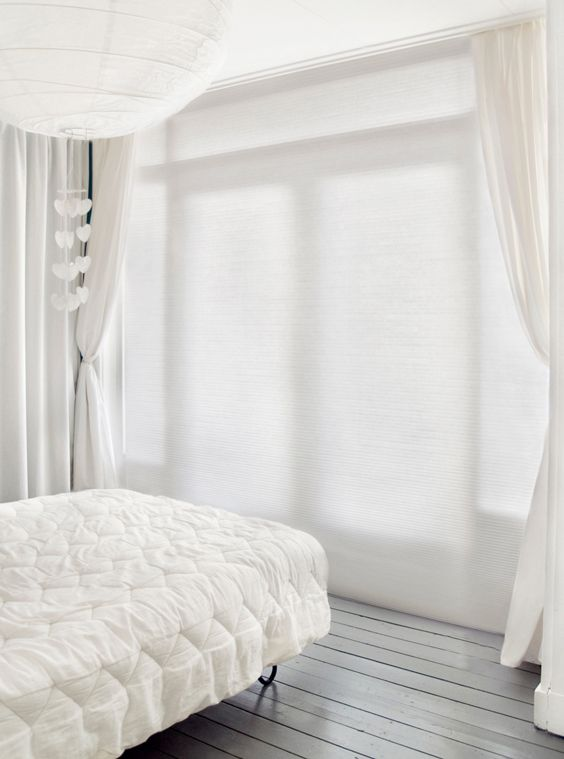 An elegant bedroom in white Honeycomb blinds suits a older style timber home.