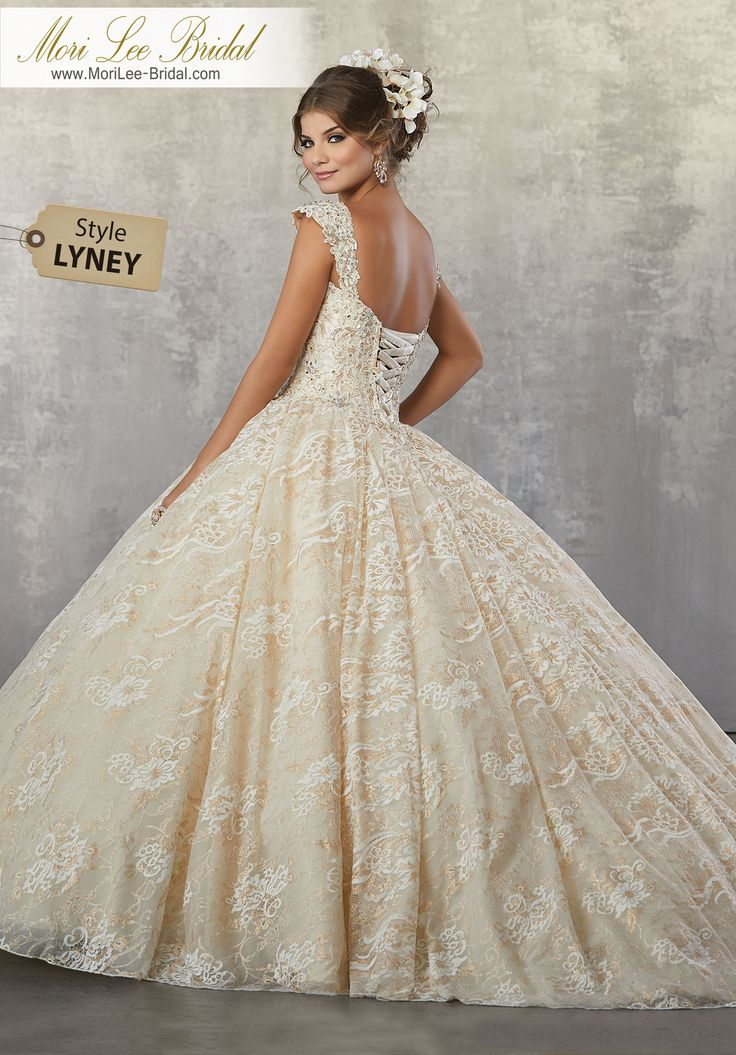Style LYNEY Crystal Beaded, Lace Appliqués on a Metallic Allover Lace Ballgown Princess Perfect, This Metallic Lace Quinceañera Ballgown Features Crystal Beaded Details and Detachable Cap Sleeves. Matching Stole Included. Colors Available: Gold