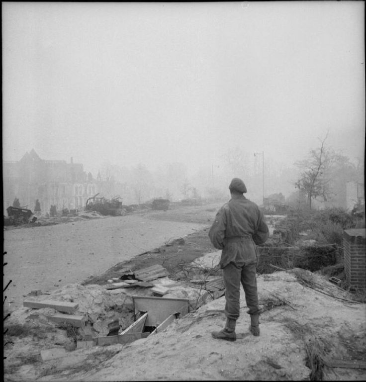 A soldier looks down the approach road to the bridge at Arnhem, scene of bitter fighting during the previous September, 15 April 1945.