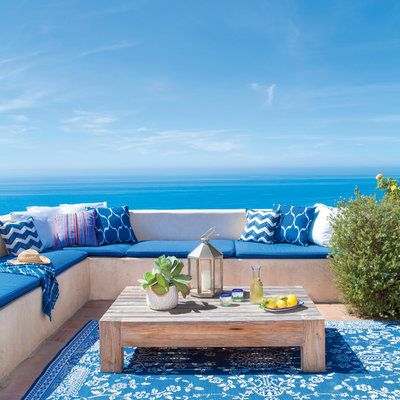 This terra-cotta tiled terrace stretches out onto a bluff, making it look like the outdoor seating area hovers over the ocean.