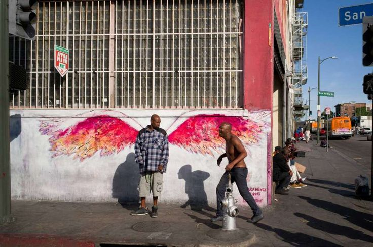 FILE - In this Monday, April 25, 2016 file photo, a man stands in front of angel wings painted by artist Colette Miller on Skid Row in downtown Los Angeles. The number of homeless people in Los Angeles County increased 5.7 percent over the past year, to report released Wednesday, May 4, 2016, but homelessness among veterans and families fell significantly.