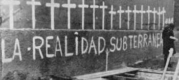 """""""La realidad subterránea"""" parte de una exposición que se intentó en una plaza de Buenos Aires hasta ser rápidamente clausurada por la policía. La obra consistía en un pozo donde por medio de fotografías de torturas y de campos de concentración nazi se aludía a la represión. Manos anónimas pegaron recortes y fotos de la situación argentina. Sobre la pared lindante con el foso se habían pintado 16 cruces blancas en homenaje a los presos políticos asesinados en la cárcel de Trelew"""