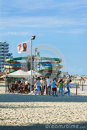 MAMAIA, ROMANIA - AUGUST 5, 2011: Group of tourists enjoy a walk on beach in Mamaia seaside resort, Romania. Mamaia is Romanias oldest, largest and best resort at Black Sea Coast.