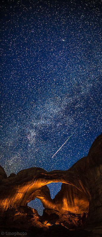Perseid meteor streaking over the lightpainted double arch in Arches National Park.