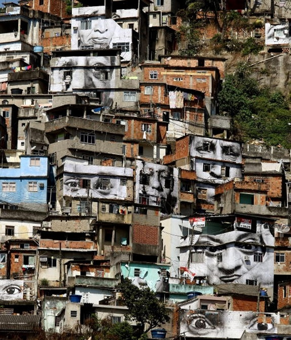 """Street Artist J R. The hills have eyes in this installation in a Brazilian favela. It's part of a larger JR project called """"Women Are Heroes,"""" with other works in Sudan, Sierra Leone, Kenya, Liberia, and elsewhere."""