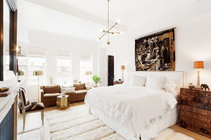 Bright bed room with white bedding, mid-century modern light fixtures, and touches of brown