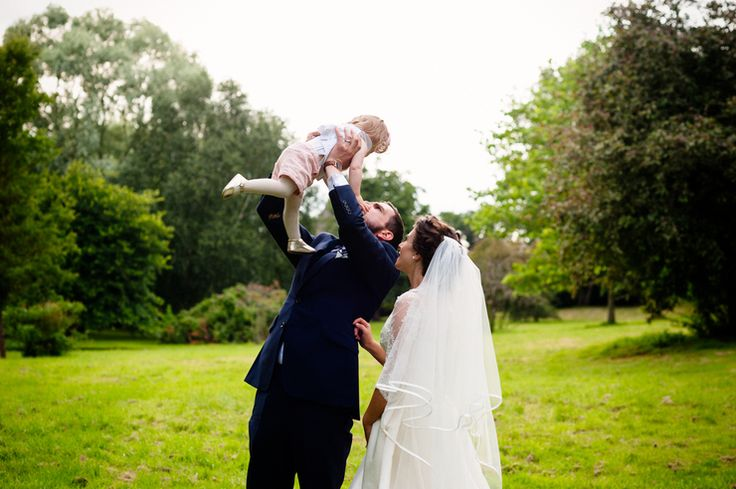 Bride wearing a dress from Grafton Manor Hotel Wedding Dress Shop, with Groom lifting child in the air at a wedding at Dewsall Court, Herefordshire - Alice's best of 2015 © Babb Photo