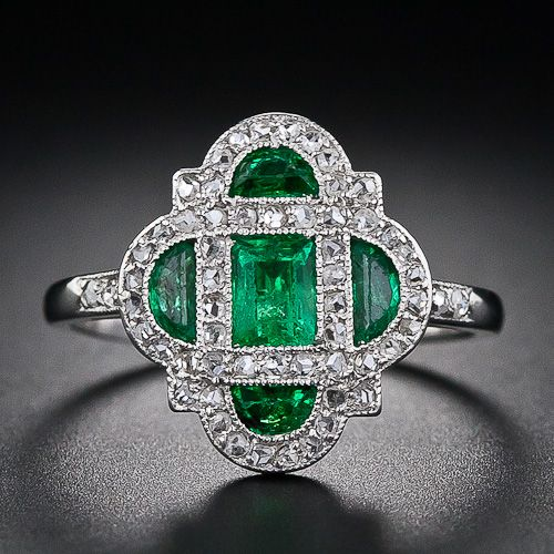 This darling and diminutive early-Art Deco delight - circa 1920 - glistens with a bright green central emerald-cut emerald and four half-moon emeralds lovingly framed in platinum and teeny-tiny rose-cut diamonds. An original and dreamy Art Deco ring - too delicate for everyday wear. The ring measures about half-an-inch in both directions.