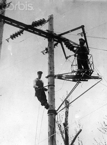 Original caption: 2/17/1921-Chicago, IL- Handling 33,000 volts of electricity, Chicago linemen work on power wires barehanded, while standing on a specially insulated wooden platform.