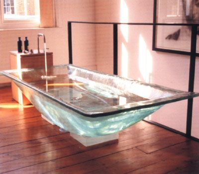 If wood is a bit too dark, maybe a glass bath sitting on a lit plinth?