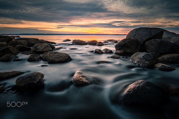 Long exposure.  Focus on the rocks in the foreground and the light from the setting sun.