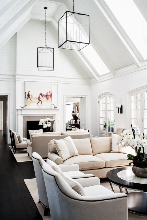 white upholstery with black nailhead trim, white tall ceilings in a double height living space. Love the large scale lanterns. Design by Sharon Mimran.