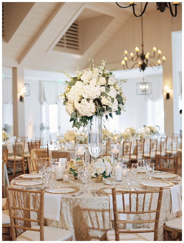 Gold, ivory and white wedding reception decor with white florals in glass vessels, place settings of gold-rimmed crystal and gold-rimmed glass chargers, floating candles and textured linens. Event design and florals by Bella Flora, image by Landon Jacob.