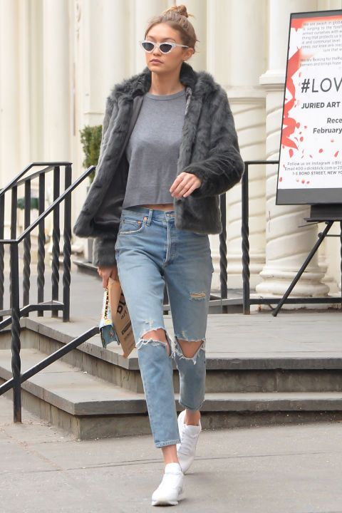 3 February Gigi Hadid was spotted off-duty in a pair of ripped denim jeans, white trainers and a grey fur coat. | @andwhatelse