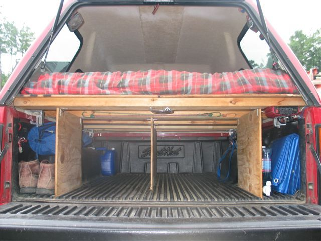 The author's truck. Note the pivoting lights (up top), sleeping platform with padding, gear alcoves and divided lower bed.