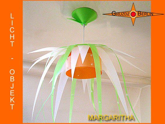 Leuchte MARGARITHA Lichtobjekt in Blütenform. Einer Margaritenblüte nachempfunden ist: Die Pendelleuchte MARGARITHA mit passendem Baldachin. Filigran schweben die Blütenblätter um den orangefarbenen Mittelpunkt, der den Raum in sein sanftes Licht taucht.